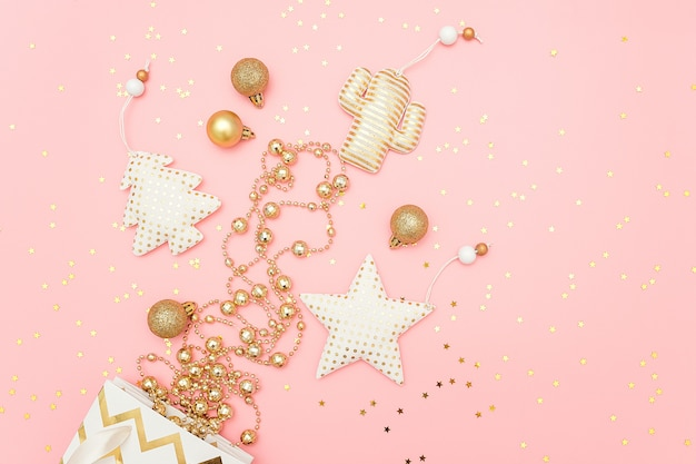 Christmas golden decorations fly out of bag and confetti stars on pink merry christmas or happy new year concept.
