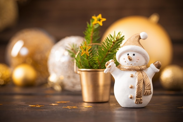 Christmas golden decorations and snowman on dark wooden table