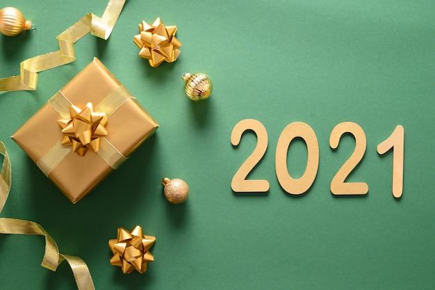 Рождественский золотой подарок и шары на зеленом цвете как знамя. новогодняя открытка 2021 года.
