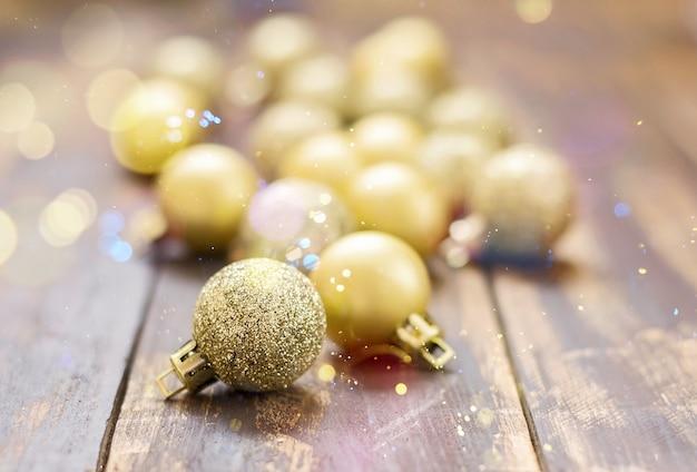 Christmas golden glittered balls on brown wooden table.