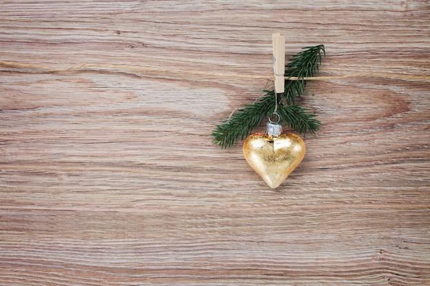 나무 배경에 빨랫줄에 매달려 상록 나뭇가지와 크리스마스 황금 심장