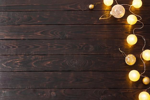 Рождественские золотые огни на темном деревянном фоне