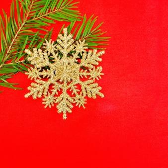 クリスマスの黄金の雪の結晶、赤い絹の背景にトウヒの枝