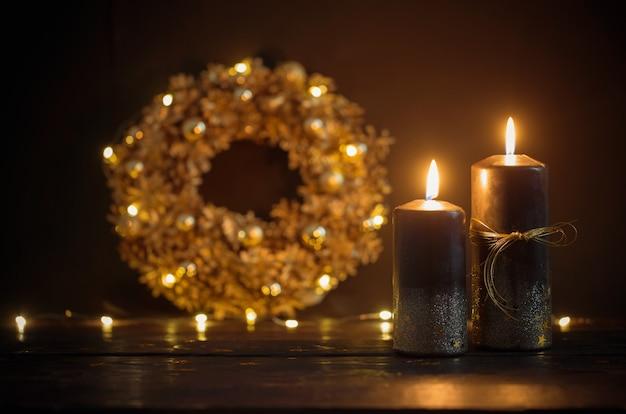 暗い木製に黒い燃えるろうそくとクリスマスの黄金の花輪