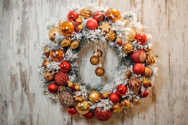 金色と赤の装飾が施された白い雪で覆われたクリスマスグリーンの人工花輪