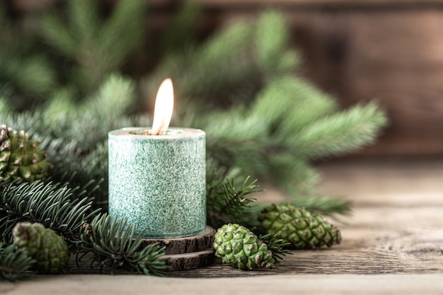 Рождественская зеленая свеча с еловыми ветками и шишками на деревянном столе, копией пространства