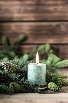 Christmas green candle with fir branches and cones on wooden table
