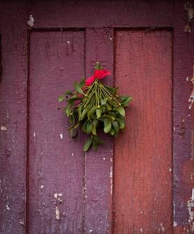 クリスマスの緑のヤドリギが古いひびの入ったドアにぶら下がっていました。