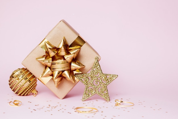 Christmas greeting card composition. craft paper gift with golden ball, confetti star and gold decoration on pink background