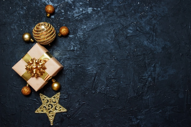 Christmas greeting card composition. gift with golden christmas decoration on dark blue background.