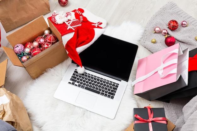 나무 배경에 크리스마스 인사말 카드, 선물 상자, 노트북 및 커피 컵. 텍스트 복사 공간이 있는 상위 뷰