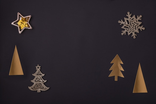 Christmas greeting card made of golden christmas decorations on black paper background.