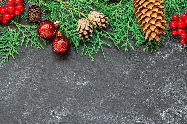 Шаблон рождественской открытки с сосновыми шишками, ветвями ели и красными ягодами на черном деревенском фоне вид сверху.
