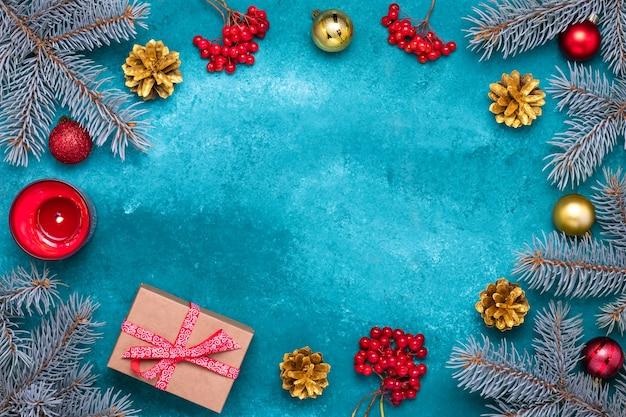 青いモミの枝と金の松ぼっくりのクリスマスグリーティングカード。赤いガマズミ属の果実のクラスター