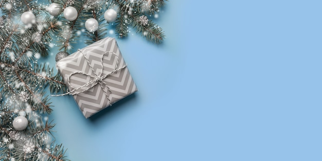 Christmas greeting card with fir branches, white gift box, snowflakes on blue.