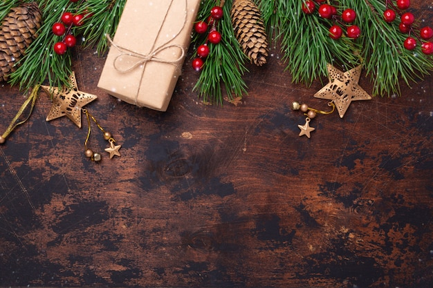 Christmas greeting card with fir tree branch, gifts and present box. wooden background. top view copyspace