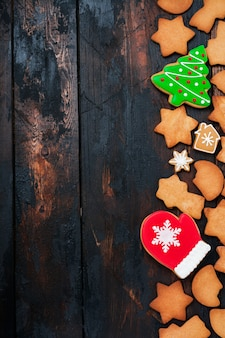 古い木の表面にジンジャーブレッドが付いたクリスマスのグリーティングカード。上面図