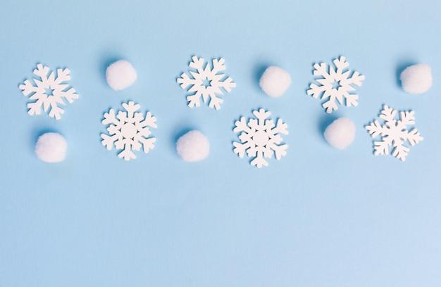 青い背景に雪片のラインとクリスマスグリーティングカード。あなたのテキストのための場所が付いているクリスマスの休日のはがき。