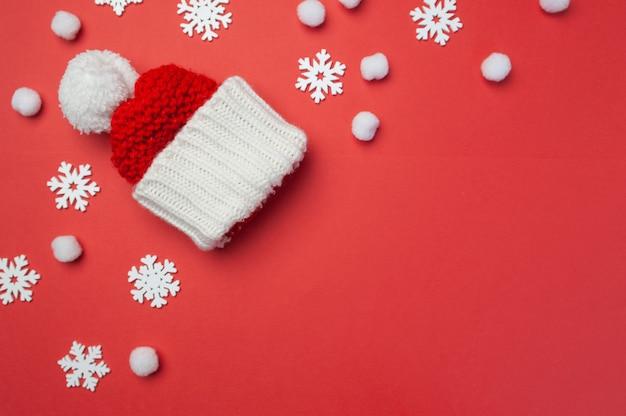 赤い帽子と赤い背景に雪片が付いたクリスマスグリーティングカード。クリスマスホリデーポストカード。