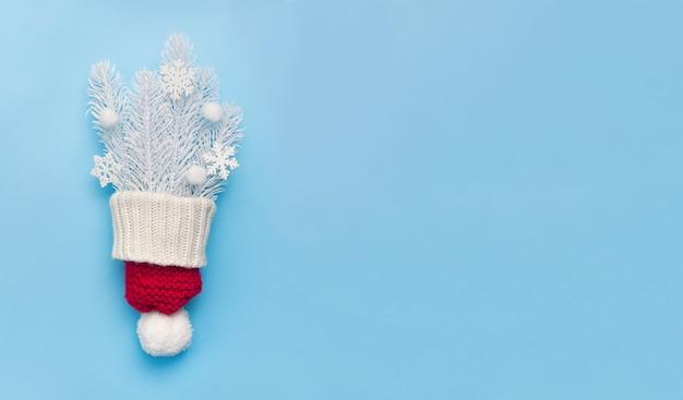 赤い帽子と白いモミの枝と青い背景に雪片のクリスマスグリーティングカード。クリスマスの休日。