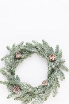 크리스마스 인사말 카드입니다. 흰색 나무 바탕에 화 환 장식입니다. 새해 개념. 공간을 복사하십시오. 평평하다. 평면도.