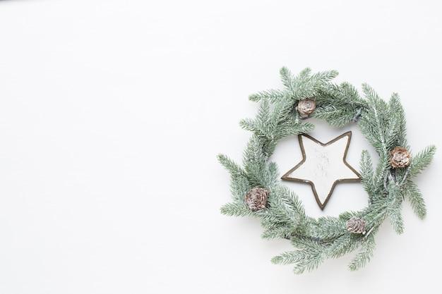 クリスマスのグリーティングカード。白い木製の背景に花輪の装飾。新年のコンセプト。スペースをコピーします。フラットレイ。上面図。