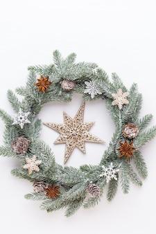 クリスマスのグリーティングカード。白い木製の背景に花輪の装飾。