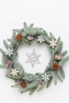 Рождественская открытка. украшение венка на белой деревянной предпосылке.