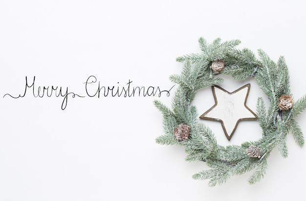 크리스마스 인사말 카드입니다. 흰색 나무 새 해 개념에 화 환 장식입니다. 공간을 복사하십시오. 평평하다. 평면도.