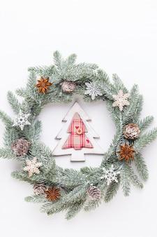Рождественская открытка. украшение венка на белой деревянной поверхности. новогодняя концепция. скопируйте пространство. плоская планировка. вид сверху.
