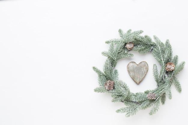 クリスマスのグリーティングカード。白い木製のテーブルに花輪の装飾。新年のコンセプトです。コピースペース。フラット横たわっていた。上面図。