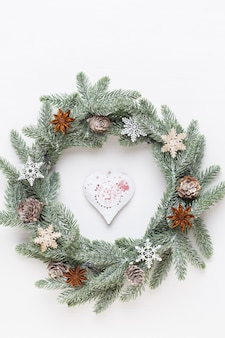Christmas greeting card. wreath decoration on white wooden background. new year concept. copy space.  flat lay. top view.