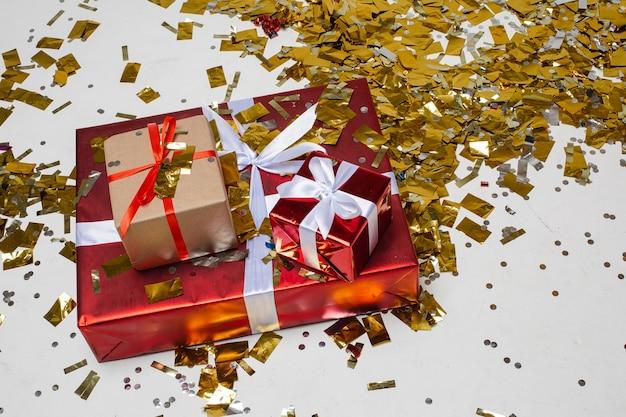 クリスマスの挨拶プレゼントボックス。クリスマスの休日の壁、金の明るいキラキラ紙吹雪でお祝いのプレゼント。