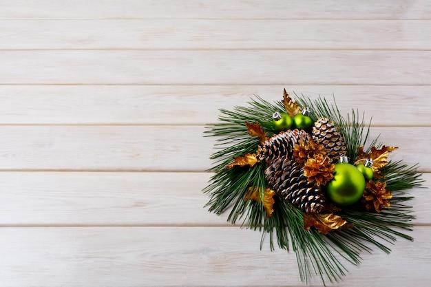Рождественская открытка с сосновыми ветками и золотыми шишками