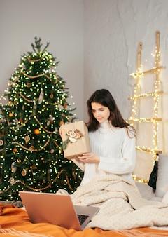 Рождественские поздравления онлайн. улыбающаяся девочка с помощью компьютерного компьютера для видеозвонков друзьям и родителям.