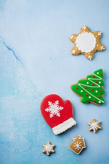 Christmas. group of gingerbreads, cinnamon, orange, toys and cup of hot chocolate on light blue.