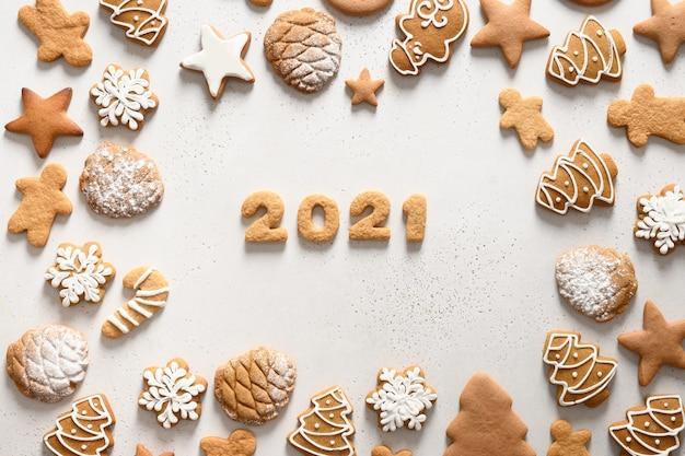 흰색 바탕에 날짜 2021 주위에 배열하는 크리스마스 수 제 쿠키. 메리 크리스마스. 위에서 봅니다. 평평하다.