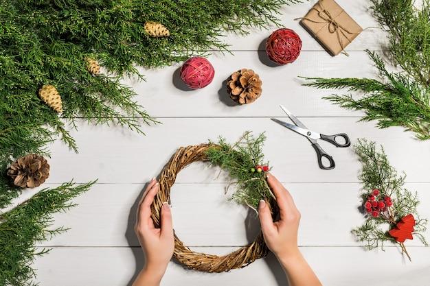 クリスマス手作りのdiyの背景。クラフトクリスマスリースやオーナメントを作る。休日の装飾のための女性のレジャー、ツール、装身具。女性の手で白い木製テーブルの平面図です。