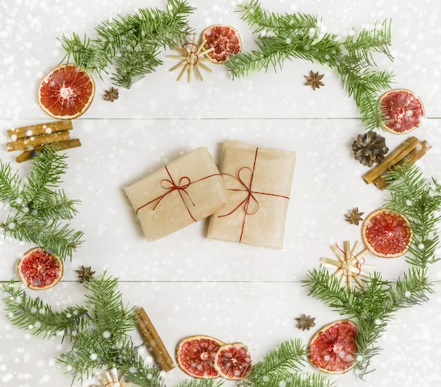 Christmas handmade gifts from kraft paper in festive wreath of spruce branches oranges cinnamon