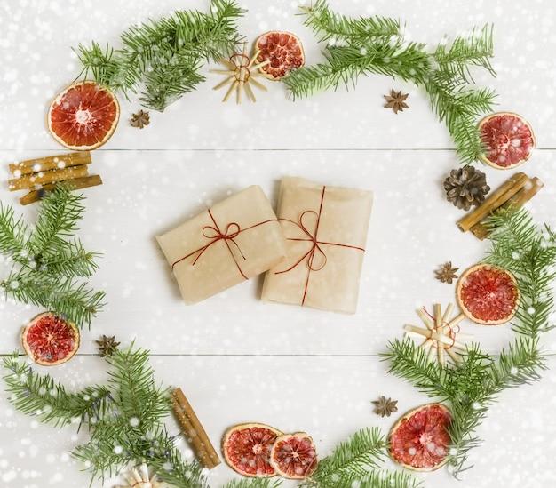 가문비나무 가지 오렌지 계피의 축제 화환에 크래프트 종이로 만든 크리스마스 수제 선물