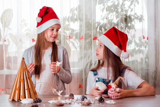 Рождество ручной работы. девочки лепят из бумаги елку и украшают ее.