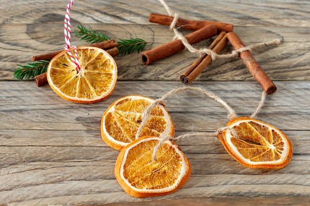 Новогодние украшения ручной работы из натуральных материалов. гирлянда и елочная игрушка из сушеных ломтиков апельсина на деревянном столе. зимний натюрморт.