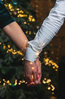 一緒に花輪の男性と女性のクリスマスの手。セレクティブフォーカス。ホリデー。