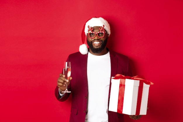 크리스마스. 파티 안경과 산타 모자를 쓴 잘생긴 아프리카계 미국인 남자, 새해 선물과 샴페인 한 잔을 들고 행복한 휴일, 빨간색 배경
