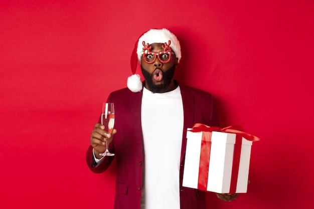クリスマス。パーティーグラスとサンタ帽子、新年の贈り物とシャンパングラスを持って、幸せな休日、赤い背景を願ってハンサムなアフリカ系アメリカ人の男