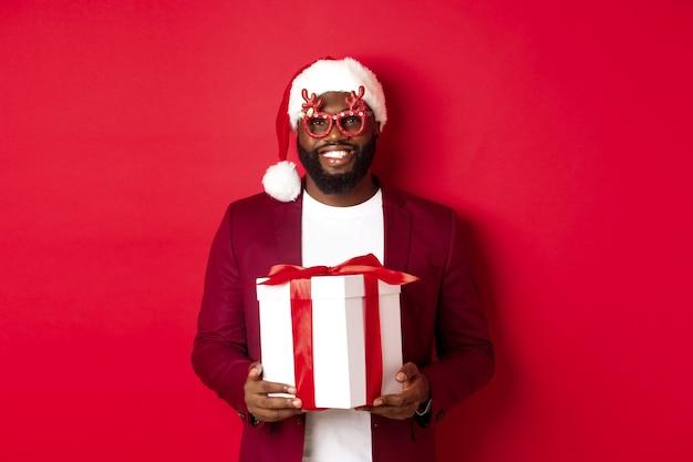 크리스마스. 파티 안경을 쓰고 새해 선물을 들고 있는 산타 모자를 쓴 잘생긴 아프리카계 미국인 남자, 상자에 선물을 들고 웃고, 빨간 배경 위에 서 있다