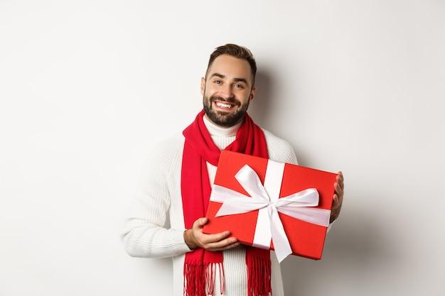 クリスマス。贈り物を持って笑顔、幸せな休日を願ってプレゼントを贈る、白い背景の上に立っているハンサムな若い男