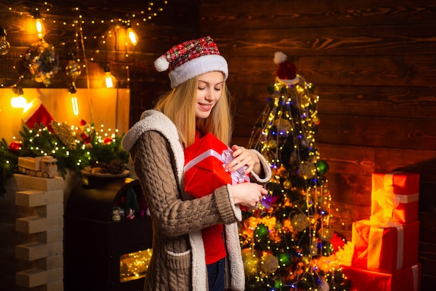 Christmas and happiness concept  a beautiful woman in santa hat helper with christmas gift in a red ...