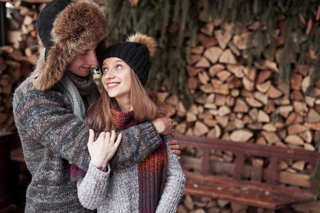 Christmas happy couple in love embrace in snowy winter cold forest, copyspace, new year party celebration, holiday and vacation, travel, love and relations