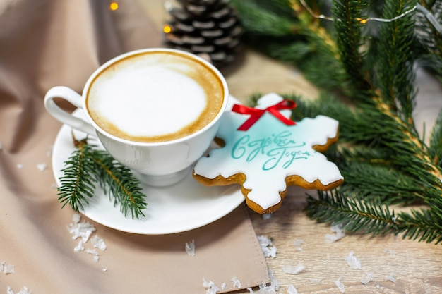 Christmas and happy new year card with cup of coffee, pine, fir branch and gingerbread